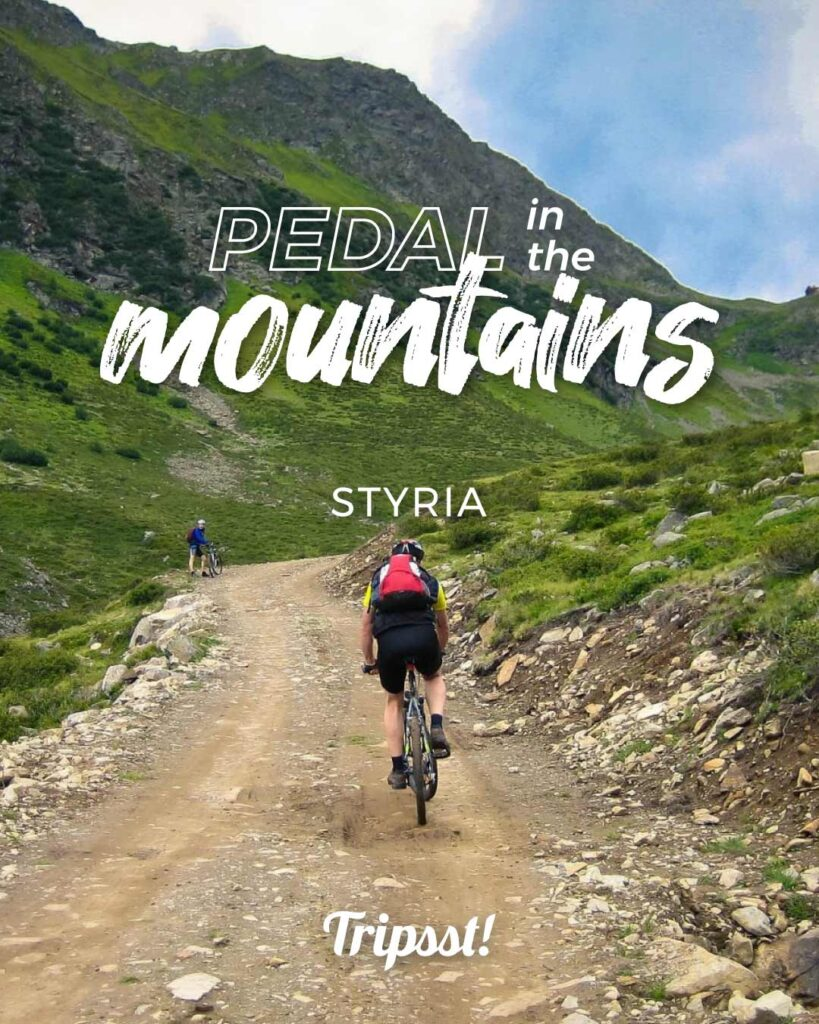 A cyclist is climbing the mountain slope