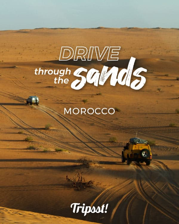Three 4WD vehicles roam into the sandy expanse of the western Sahara, near the Moroccan town of Zagora