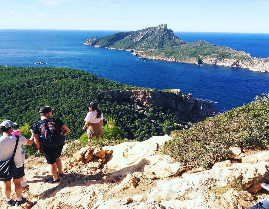People from the top of a rocky mountain in Sant Elm with a blue sea landscape