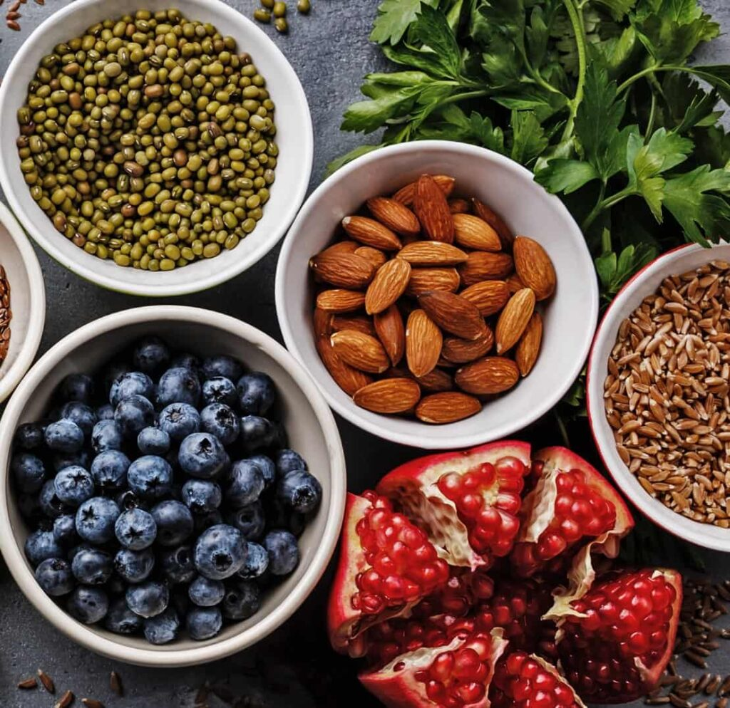 White bowls contain different products: green peas, blackberries, and almonds.