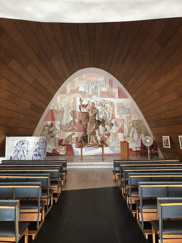 Worship area at the chapel in Pampulha, with black leathered cushions and a mural that features St. Francis of Assisi.