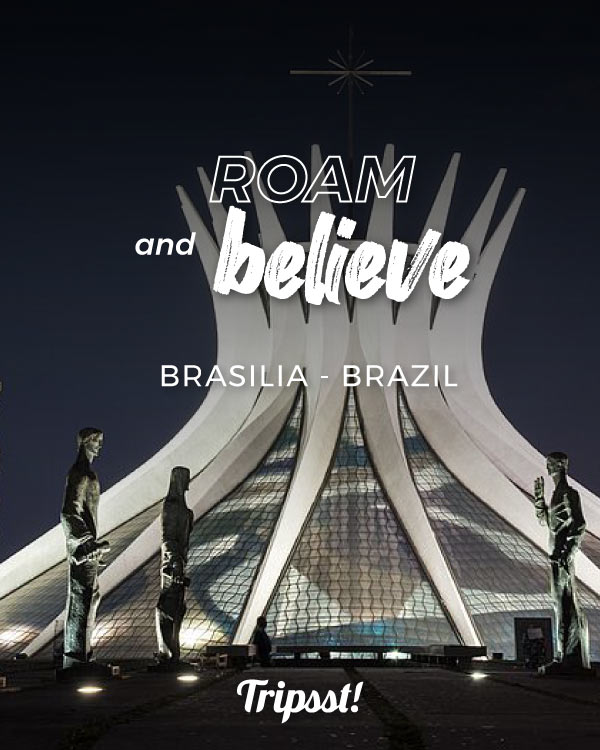 Nocturnal view of the Brasilia Cathedral, with statues in the foreground