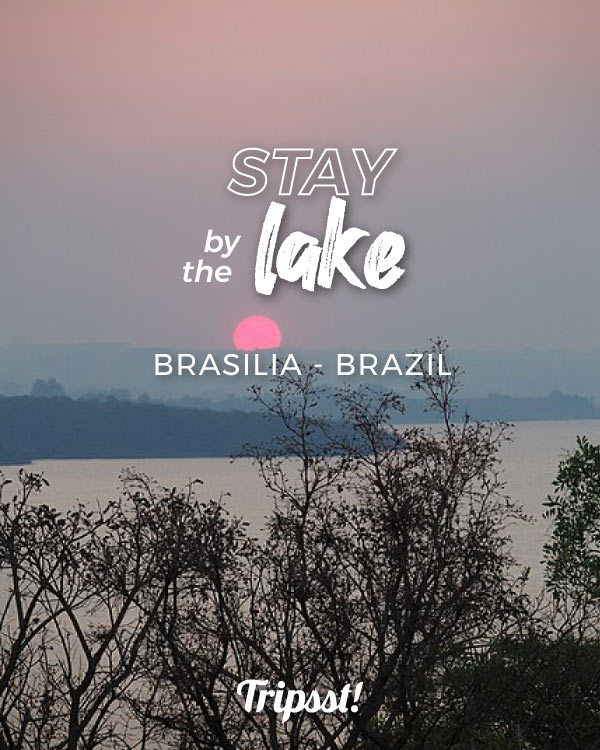 A pink sun sets as it is seen from the forested shores of Lake Paranoá