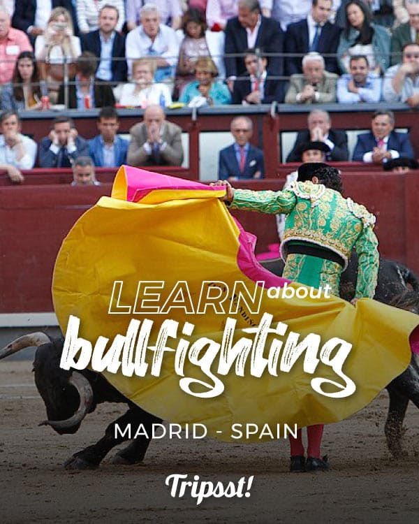 Dressed in green-and-gold, a bullfighter surrounds a bull with a yellow cape