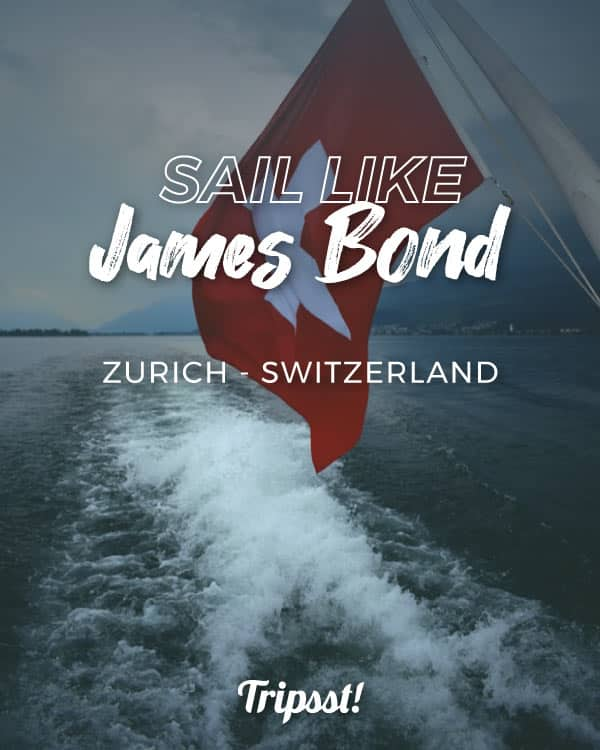 Rear of a yacht on a lake, with the Swiss flag on one side, with mountains in the background