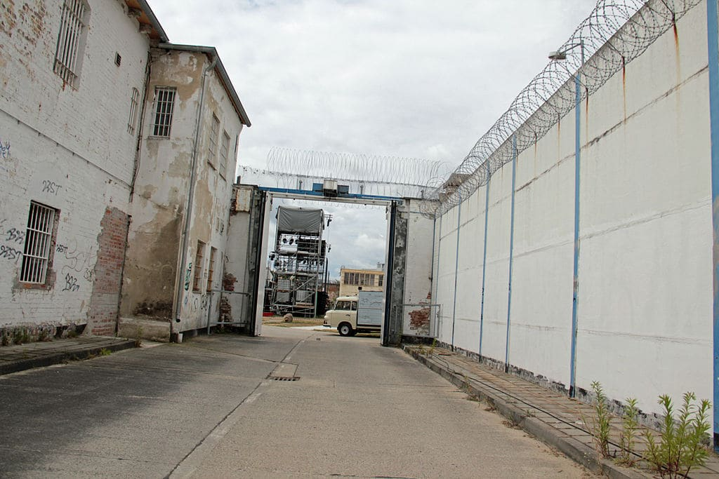 Way leading into a prison, with derelict walls on both sides, topped with barbed wire