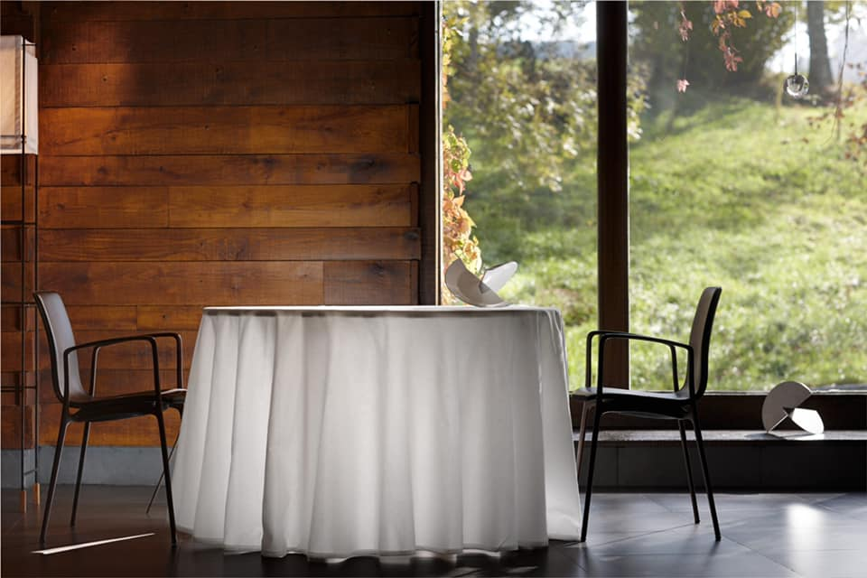 Lone table for two set against a wooden wall and wide window