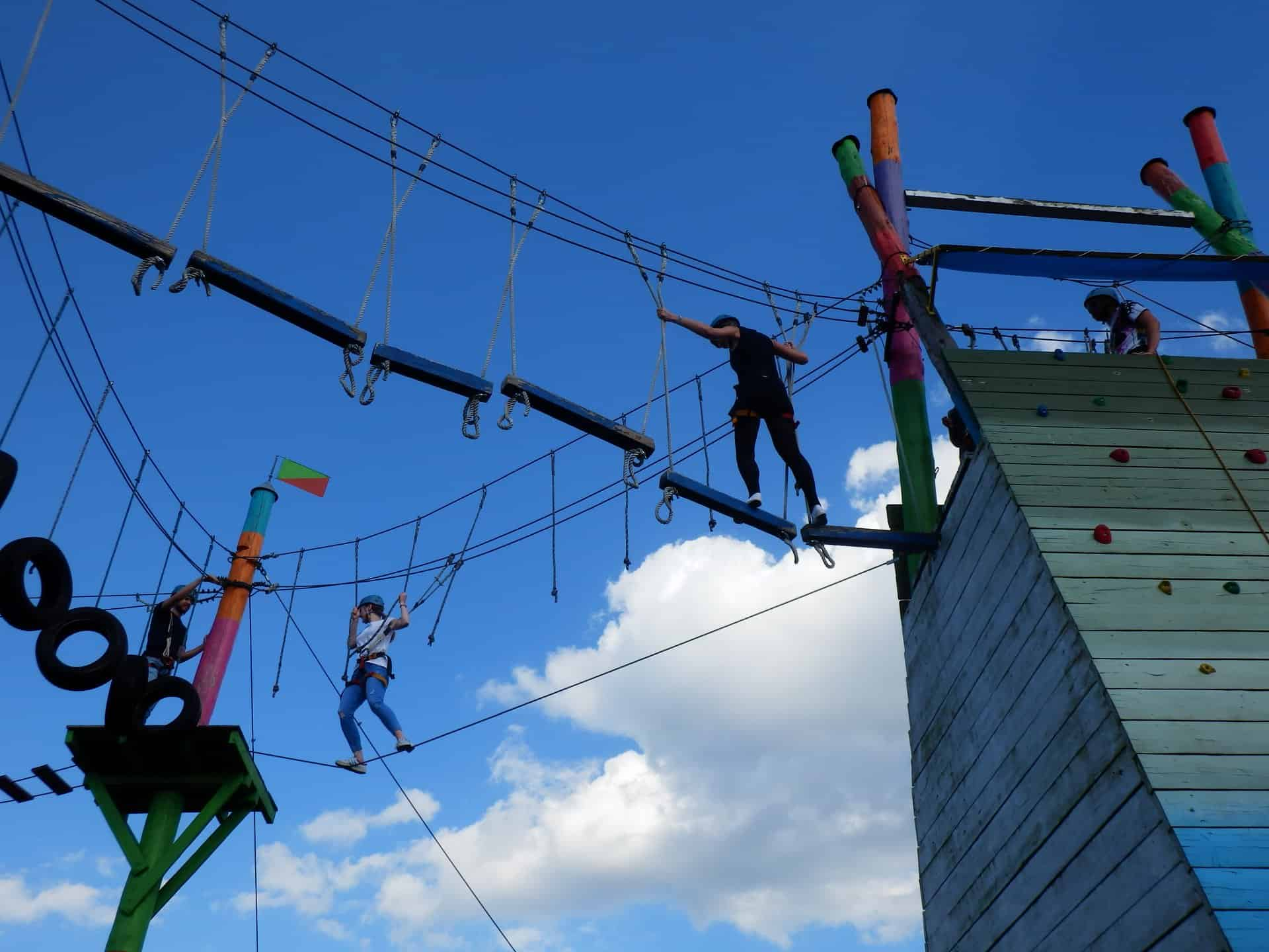 People are seen going through a wire attraction, while being strapped on