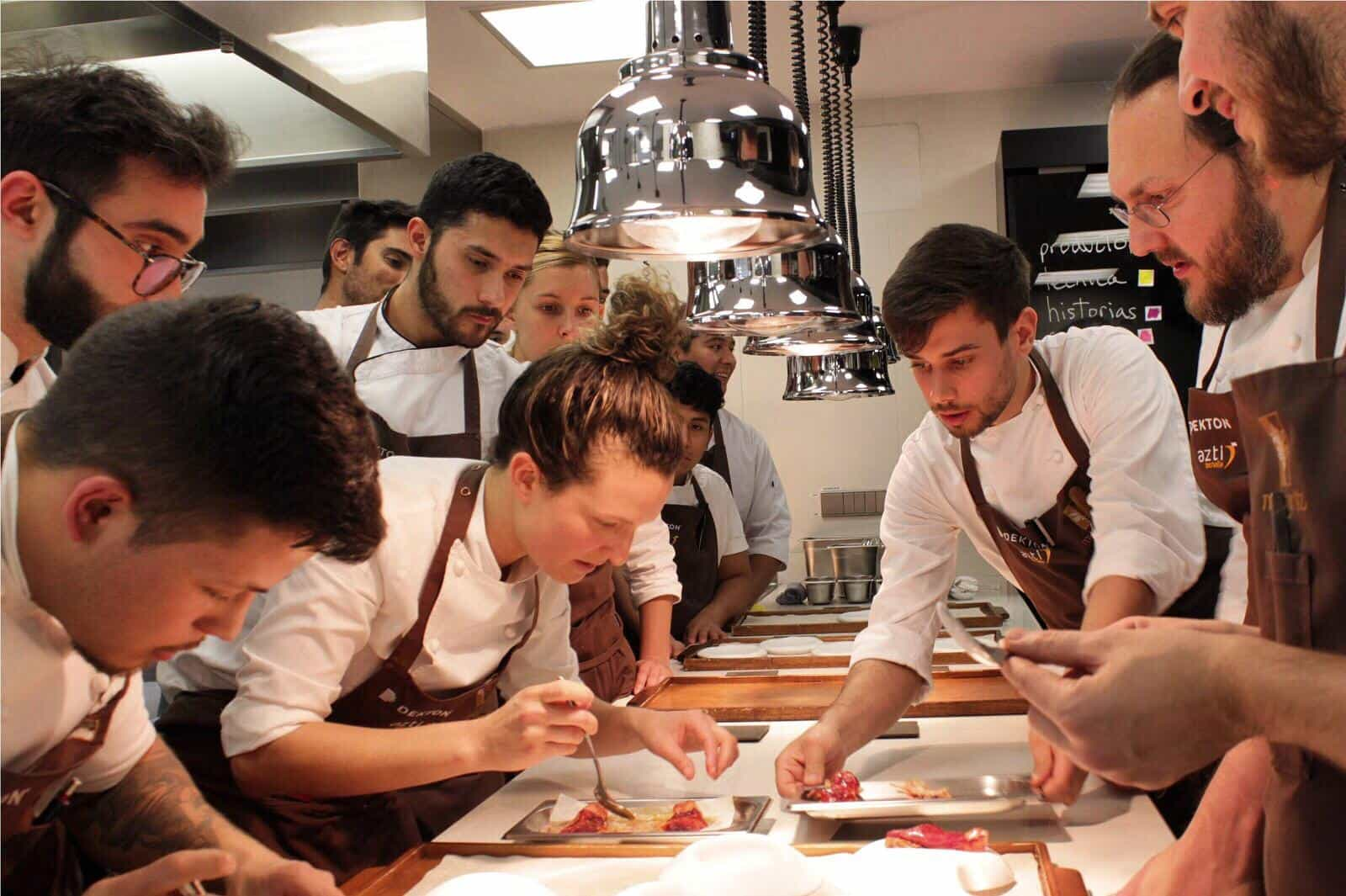 A group of chefs is seen working on gourmet dishes