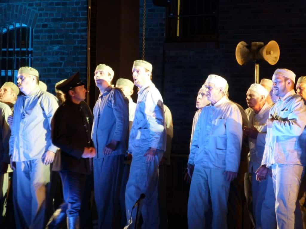 Dressed up as prisoners, a choir performs to an audience