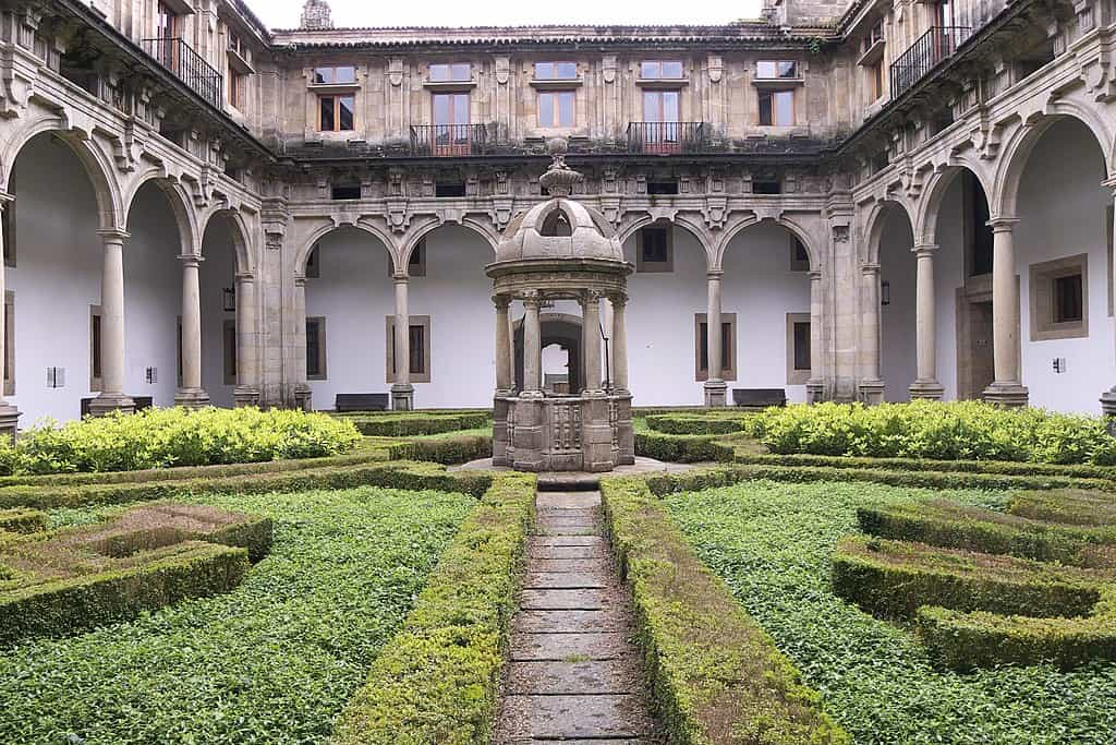 Stone fountain visible in the center of a gardened courtyard