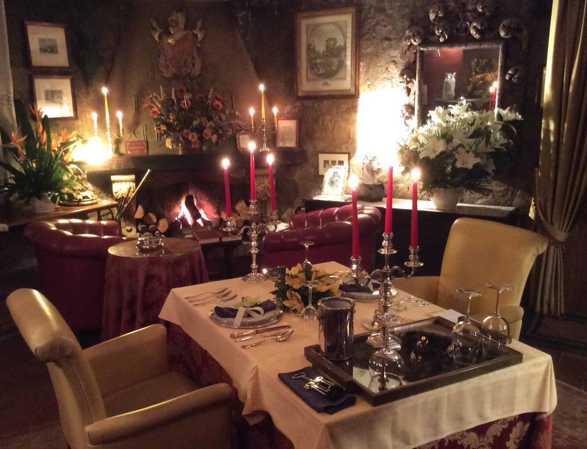 Candlelit table, with floral arrangements in the background