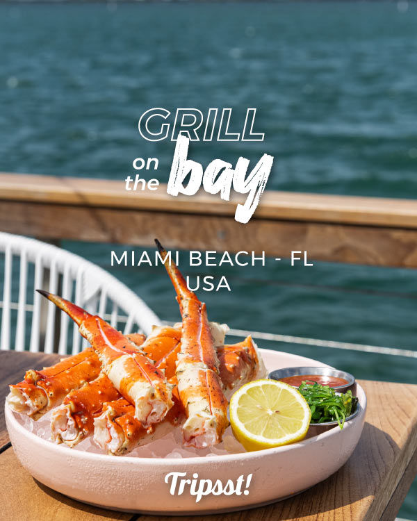 Over a wooden table and next to the water, a platter with grilled crab