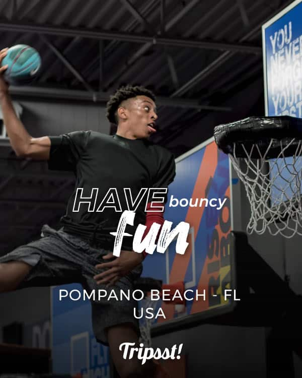 A young man jumps from a trampoline in order to score, in a bouncy basketball court.