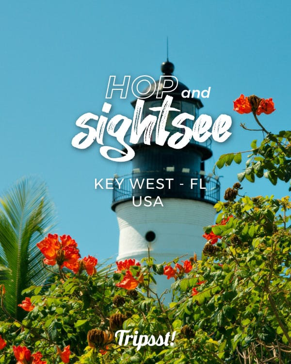 A white lighthouse towers over flowery gardens in Key West, Florida.