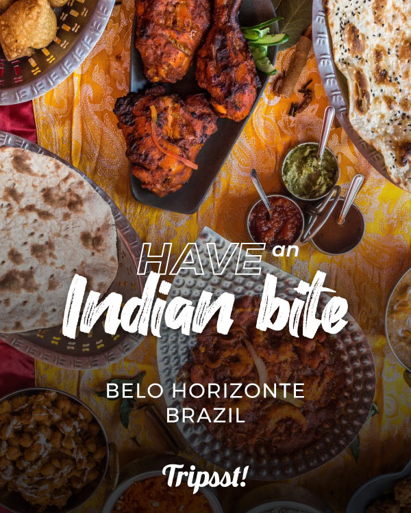 Over a table, different plates are filled with Indian recipes.