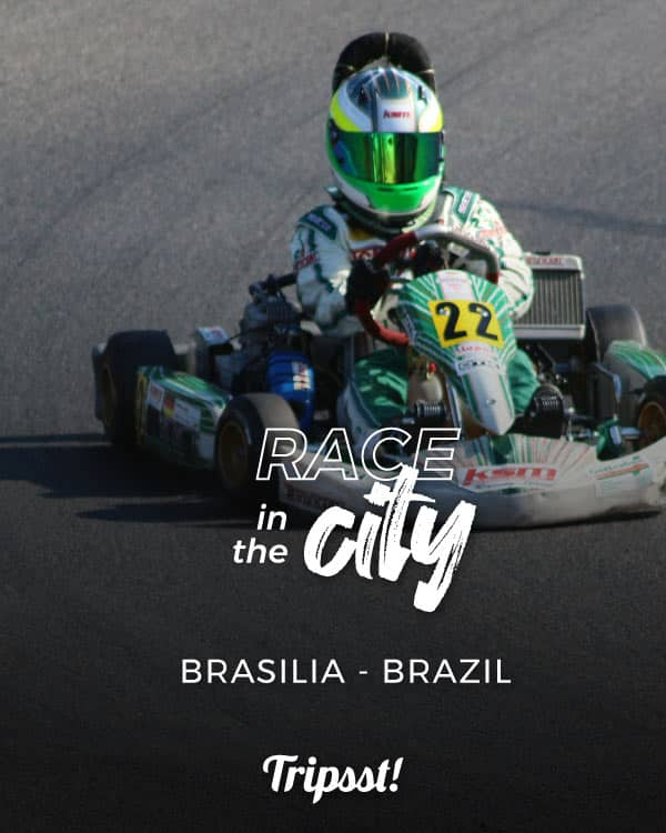 A driver, clad in a green and white uniform, drives a go-kart.
