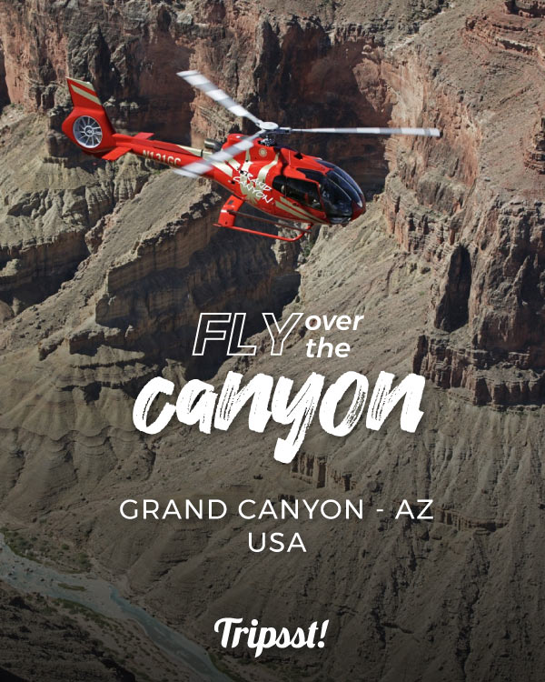 Red helicopter seen hovering over a deep canyon river