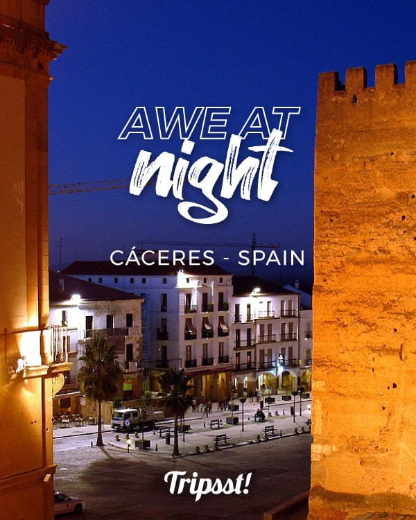 Nighttime view of historical walls against a more recent building