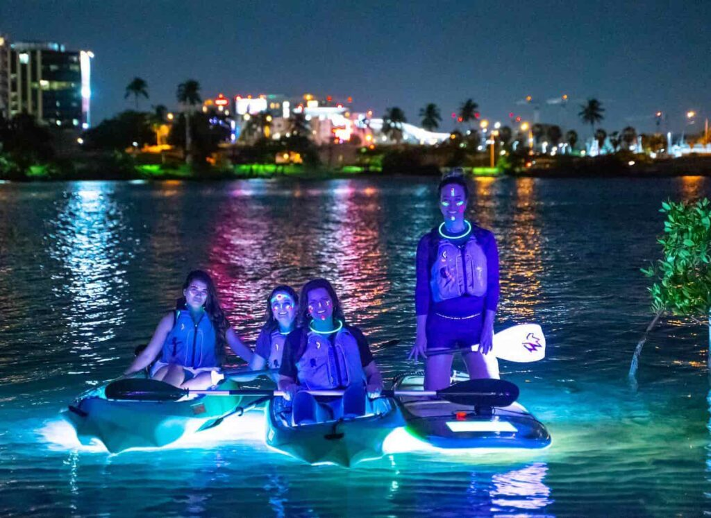 women with fluorescent accessories are kayaking