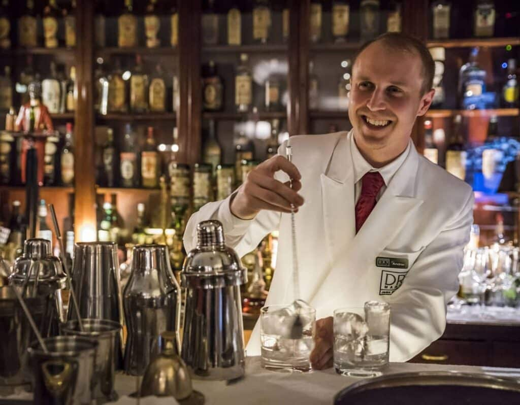 A bartender is smiling and preparing a cocktail.