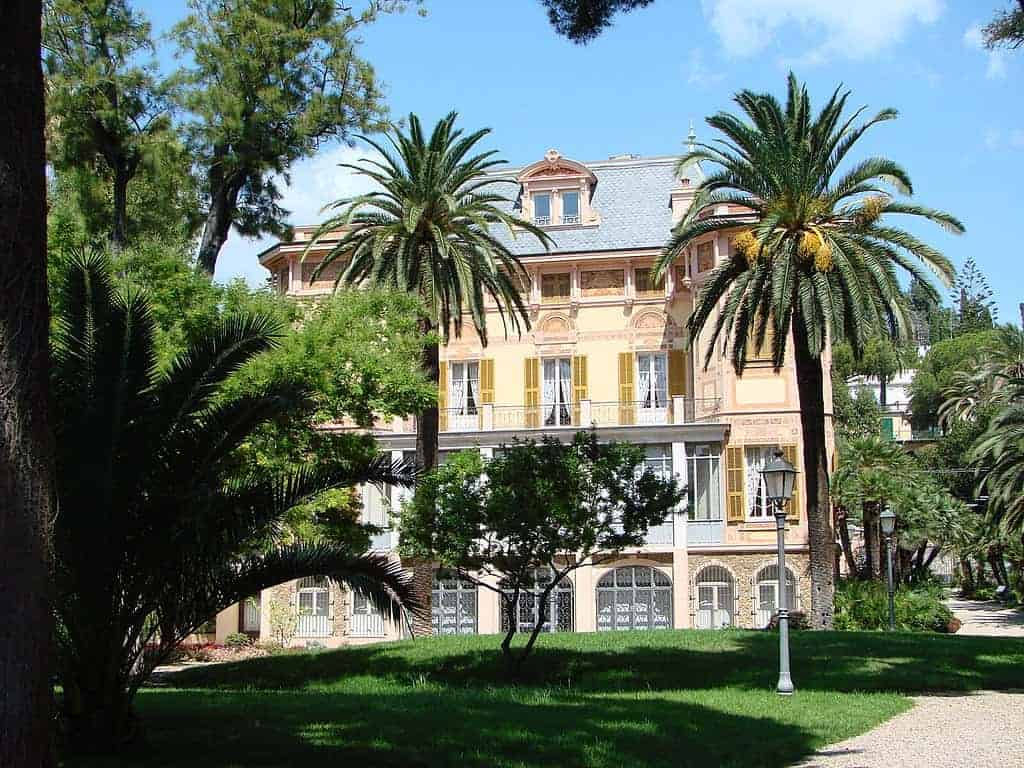 Four-storied mansion seen behind a couple of palm trees