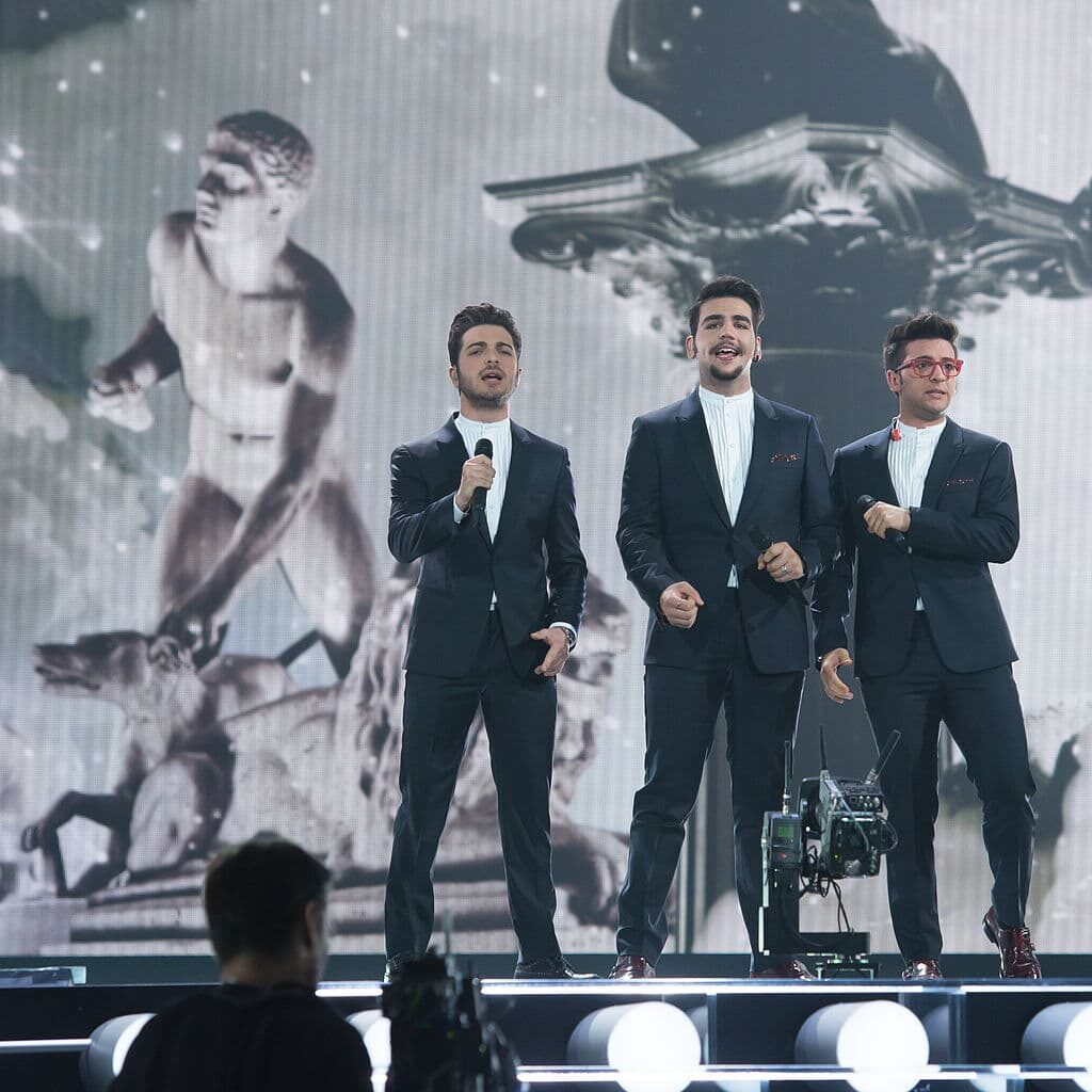 Three singers, dressed in suits, perform on stage