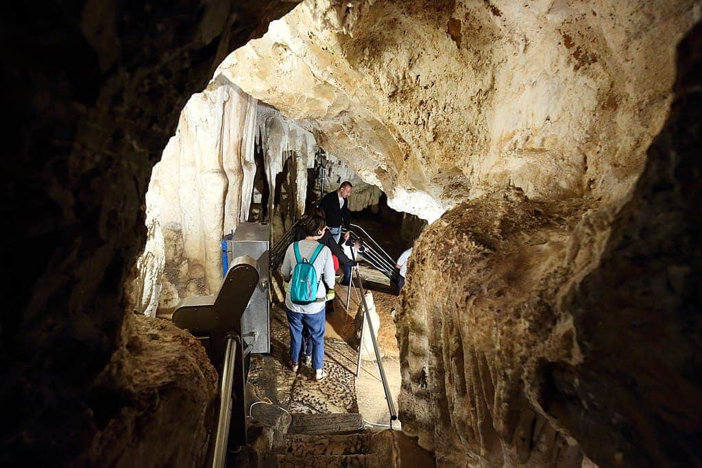 People are seen walking inside a cave, with visible stalactites