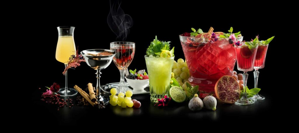 7 different types of cocktails posing in a background on a black background.