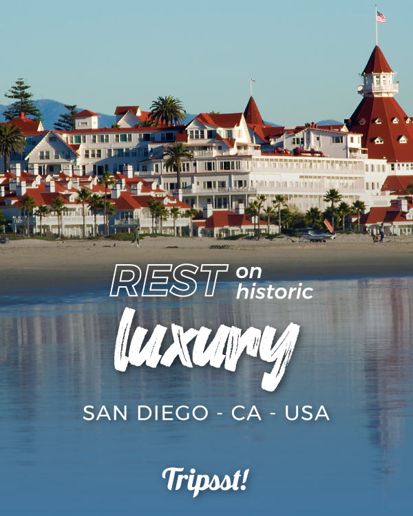 From the waters of the Pacific Ocean, the white Victorian architecture of the Hotel del Coronado features intense red roofs.