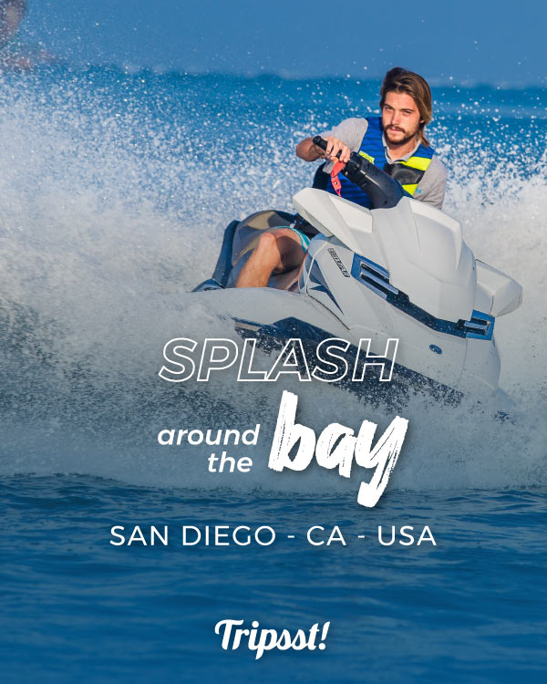 A man is seen riding a jet ski over blue waters.
