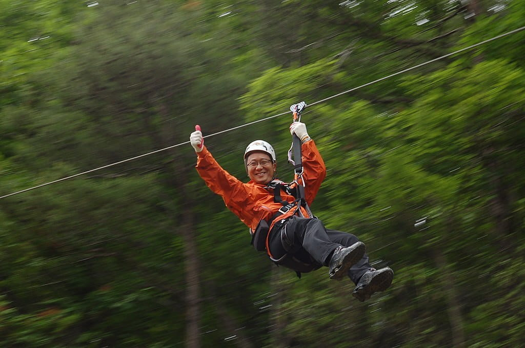 An Asian man, wearing protective gear, zips down the line.