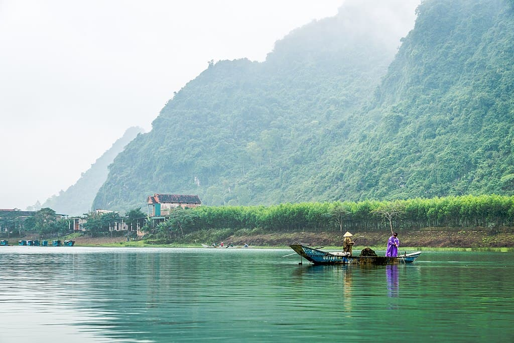 Two men row on a boat over a river, with a village in the misty background