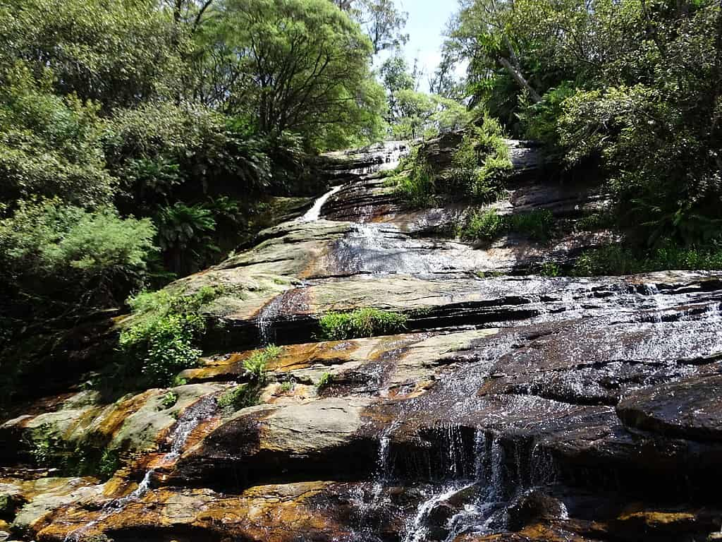 Water runs, in a cascade, down a slope of rock