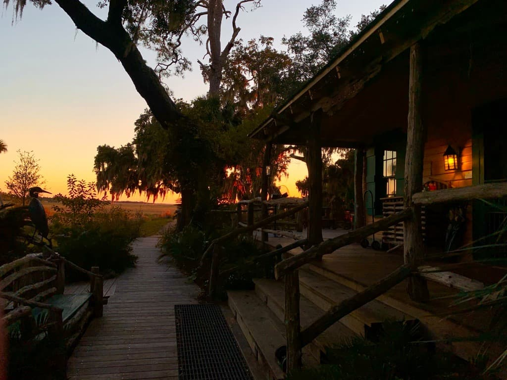 Sunset view of a wooden lodge, next to mossy cypress trees