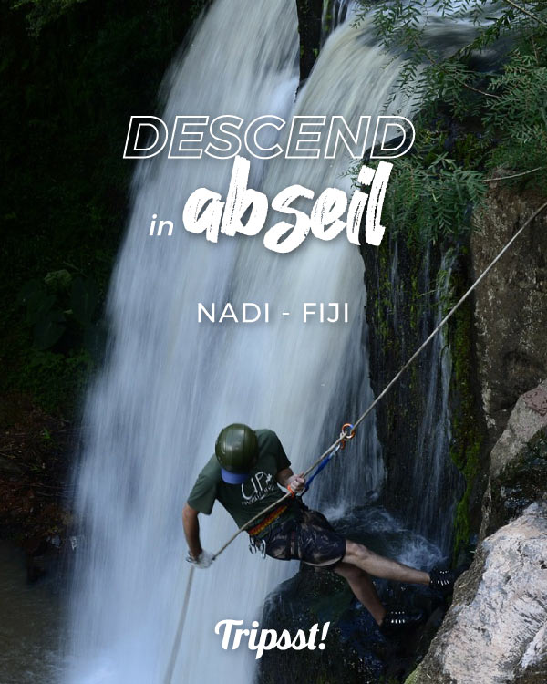 Male tourist descends next to a waterfall